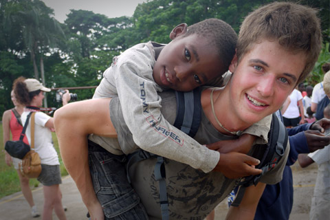 high-school-volunteer-with-african-child-on-back